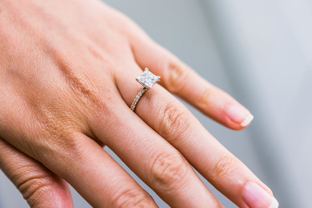 A woman with a diamond ring on her finger.