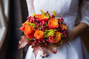 Woman's hands holding orange flowers wedding bouquet Fall Wedding Ideas Preusser Jewelers