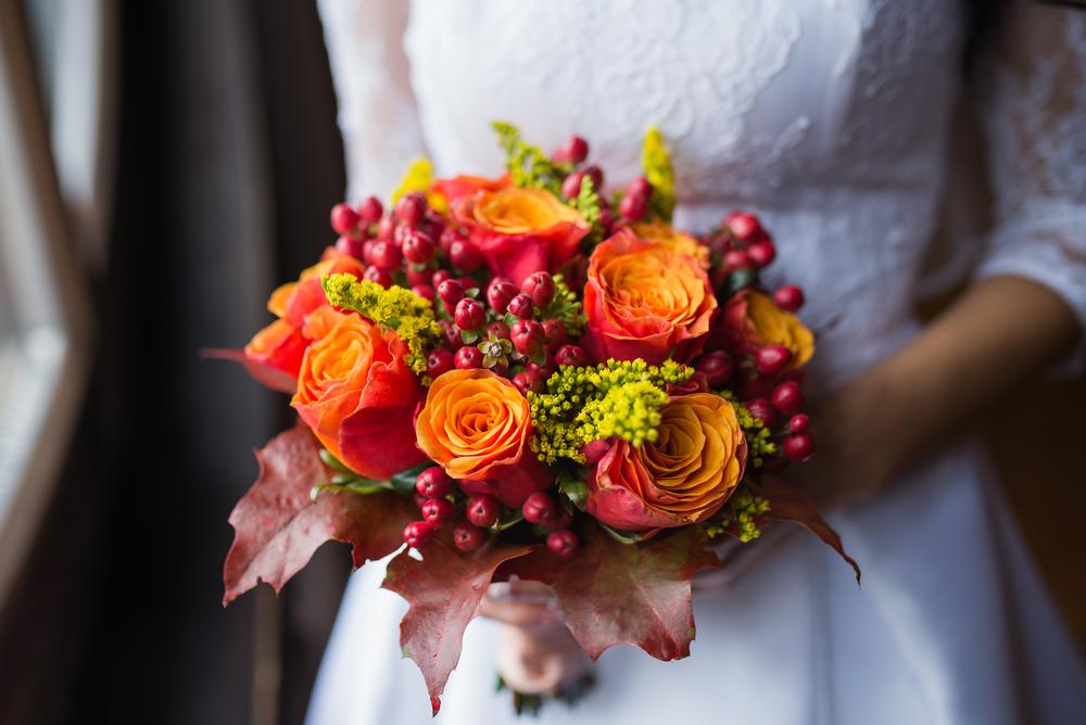 Woman's hands holding orange flowers wedding bouquet Fall Wedding Ideas Preusser Jewelers