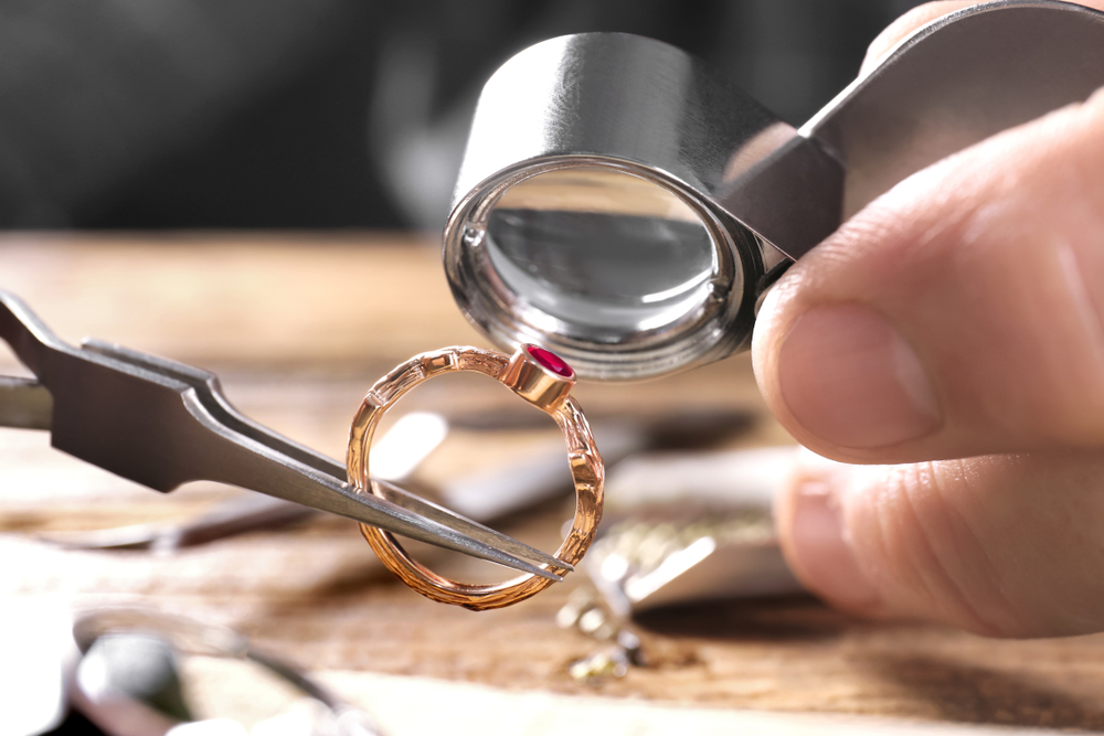 Male jeweler examining a gold ring with a red gem