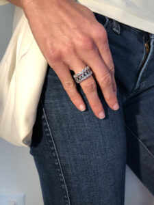 Stackable rings on woman's hands resting on her pocket